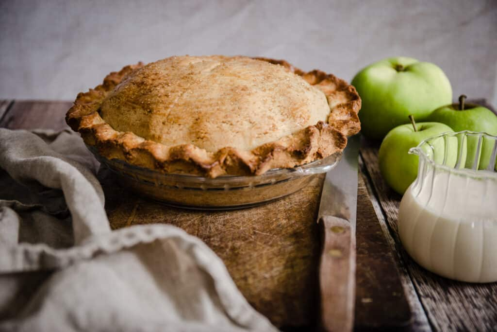 side view of apple pie on a wooden board next to apples and cream