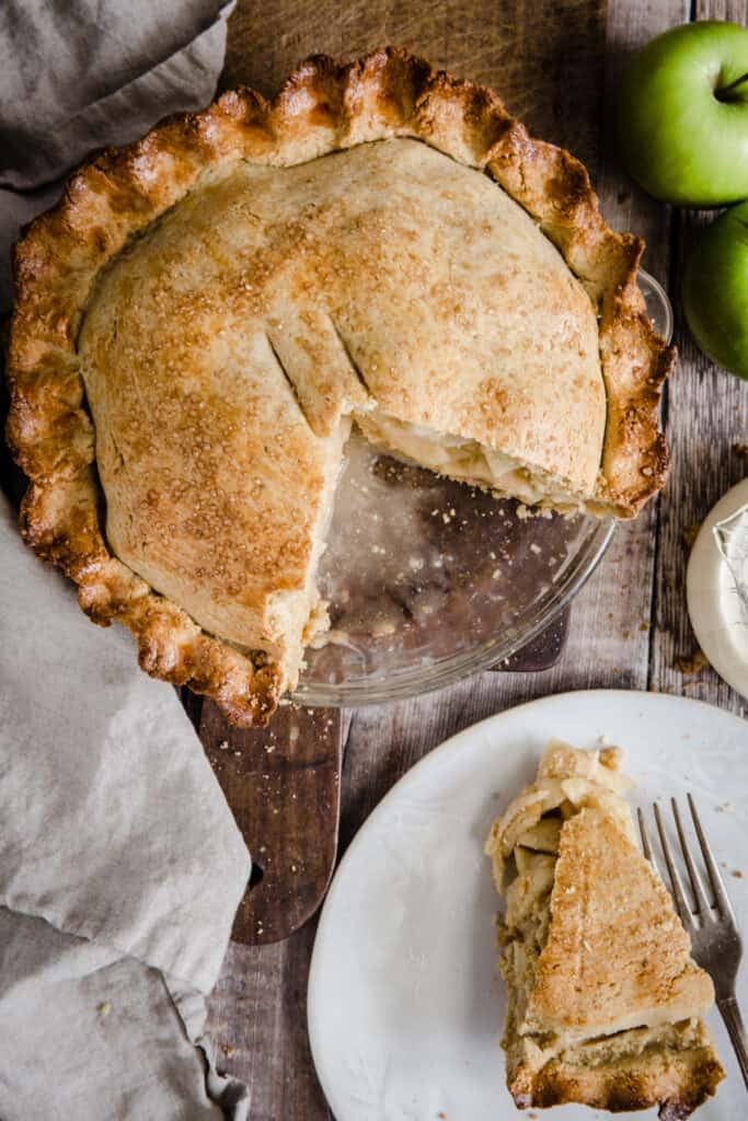 Overhead of cut Apple pie on a wooden board next to apples and cream