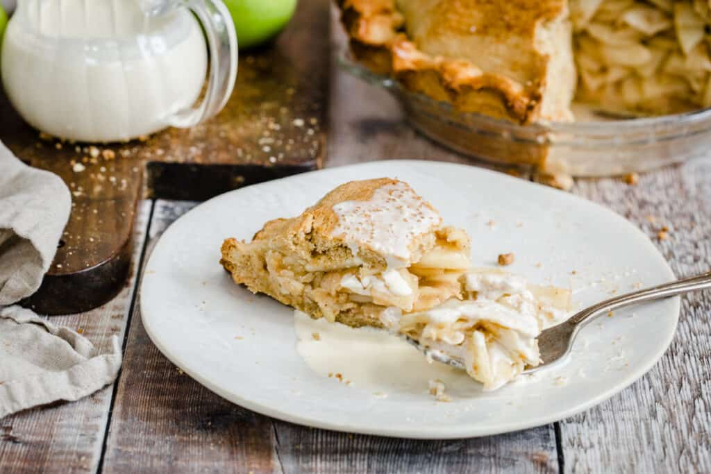 slices of apple pie on a plate with cream and a fork