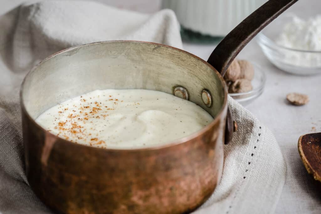 white sauce in a saucepan surrounded by ingredients
