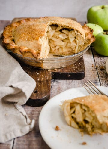 Cut open apple pie on a wooden board next to apples