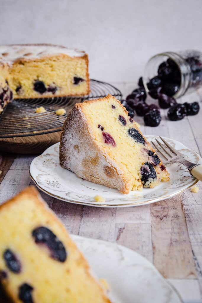 Cherry Cake sliced on a plate in front of whole cake